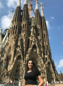 woman with long black hair standing in front of a tall cathedral
