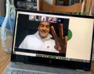 laptop screen with man in white sweatshirt giving peace sign on the screen and three other virtual meeting attendees