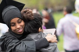 two students from different cultural backgrounds hug each other