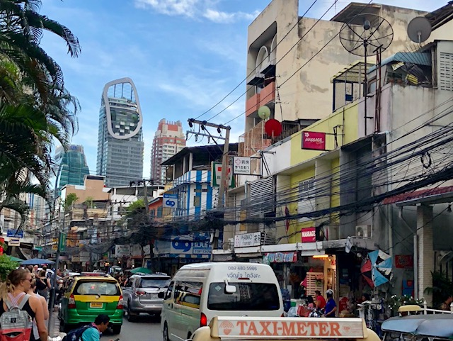 A photo taken of a busy downtown street in Bangkok. The street is full of cars and taxis. The buildings lining the street are about three or four stories high. Young blond-haired woman and a couple of other people are walking on the side walk.