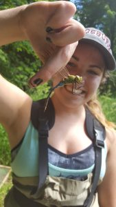 Photo of Holly Kundel holding a dragonfly