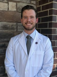 Zach Juaire standing in a white dental coat in front of a brick wall.