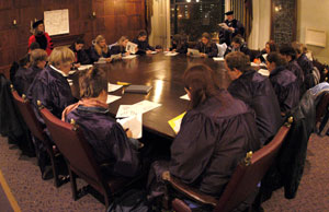 students wearing academic gowns around a table