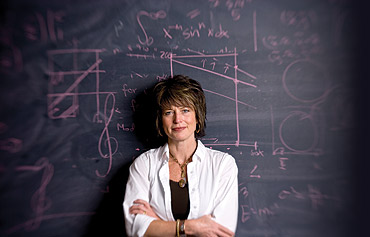 Tracy Bibelnieks stands in front of a chalk board