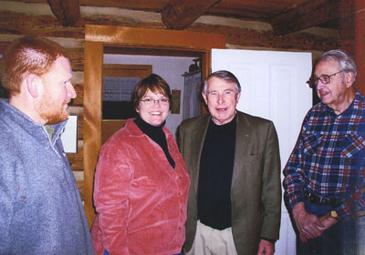 David and Margaret Anderson Kelliher join colleague Martin Sabo and Vern Sommerdorf at the log house