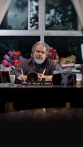 Bill Green sits at his desk