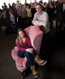 Students sits in chair with crowd of people behind her